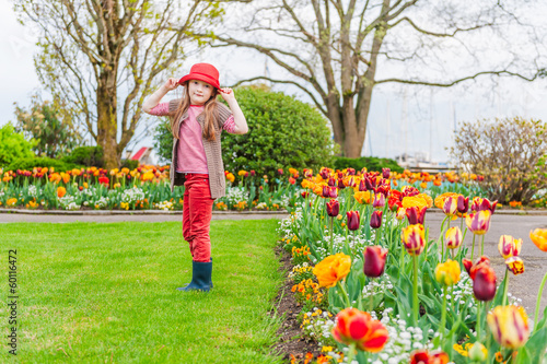 Spring portrait of a beautiful little girl in a red hat