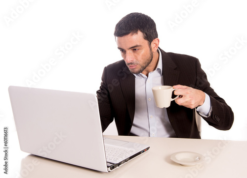 business man drinking coffee working on laptop