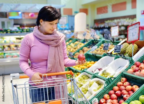 pretty woman choosing apple at fruit supermarket