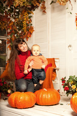 Beautiful woman with a child on the front porch with pumpkins au