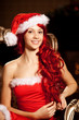 Young beautiful smiling santa woman near the Christmas tree. Gir