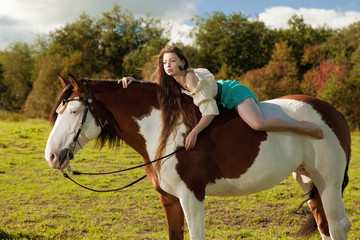Beautiful woman with a horse in the field. Girl on a farm with a