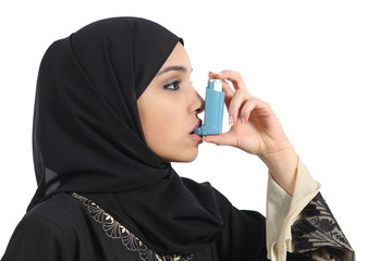 Saudi arabian woman breathing from an asthma inhaler