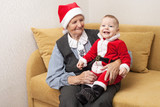 Baby boy in Santa costume with his great grandmother