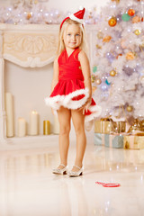Beautiful little Santa girl near the Christmas tree.  Happy gir