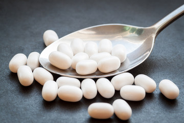 White pills in spoon on dark background.