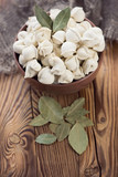 Raw pelmeni with dried bay leaves, vertical shot
