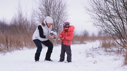 девушка и ребёнок веселятся зимой на природе