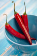 Red chili peppers in a turquoise glass bowl, close-up