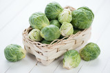 Wicker basket with fresh brussels, white wooden background