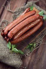 Vertical shot of smoked sausages, wooden background, above view