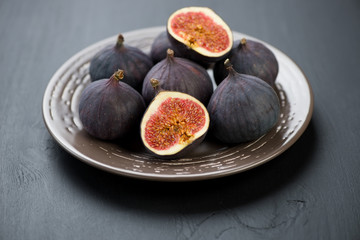 Plate with ripe figs over black wooden background
