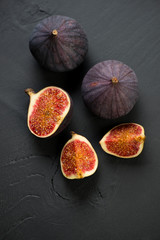 Fig fruits over black wooden surface, above view