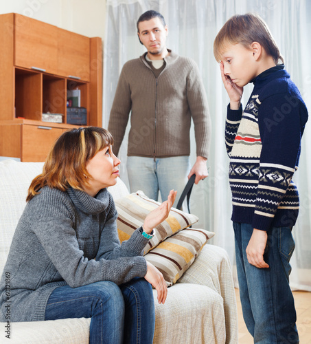 Mother and father scolding teenager boy