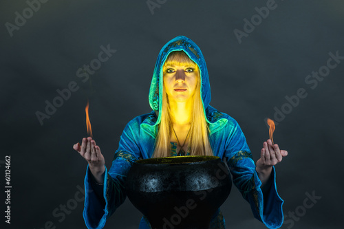 Witch with fire in hands creates a spell