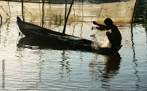 fisherman sitting on row boat, pick up the net