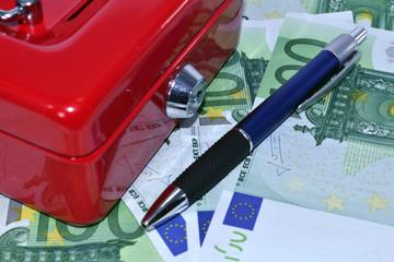 Dinero con caja fuerte y bolígrafo