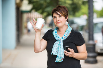 Woman With Mobilephone And Coffee Cup Waving