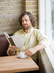 Man With Coffee Cup Reading Book In Cafe