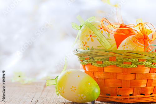 easter basket and eggs  on wooden board