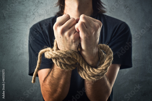 Male hands tied with a rope