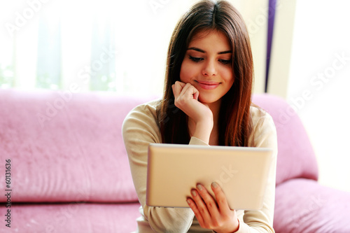 smiling woman using tablet computer at home
