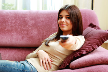 Young happy woman lying on the sofa with remote control at home