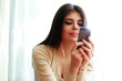 Young happy thoughtful woman using smartphone