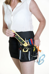 Woman wearing tool belt and holding safety googles