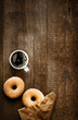 Sugared doughnuts and coffee on rustic wood