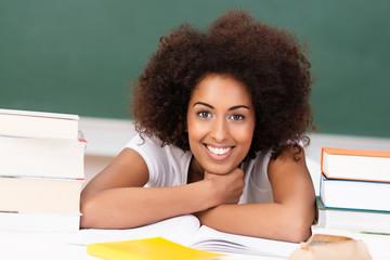 studentin mit afro-frisur zwischen bücherstapeln