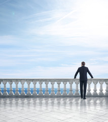 businessman standing on a terrace overlooking the sea