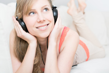 Young beautiful woman enjoying the music at home