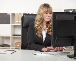 Pretty blond secretary working at her desk
