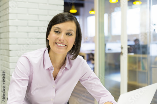 Pretty Smiling businesswoman working in office, looking camera