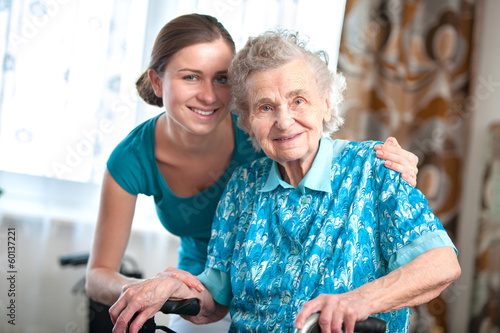 senior woman with her home caregiver - 60137221