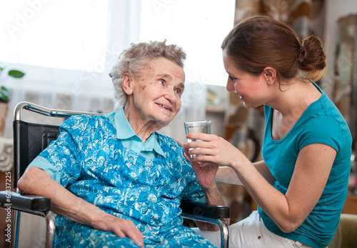 senior woman with her home caregiver - 60137225