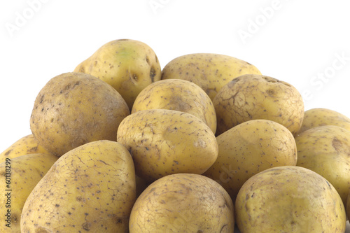 Heap of many ripe brown potatoes isolated close up