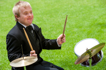 Disabled boy playing drums.