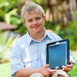 Handicapped boy holding tablet outdoors.