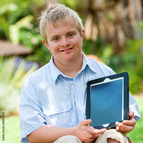 Handicapped boy holding tablet outdoors. - 60139200