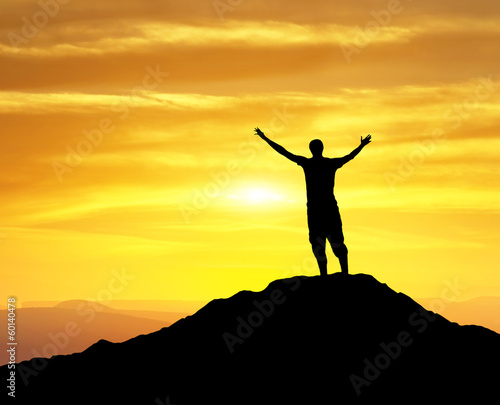 Silhouette of a winner on the mountain top