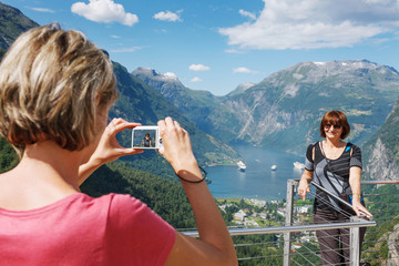 Tourists taking photo against Geirangerfjord