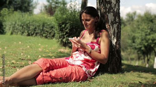 woman sitting under the tree and using her cellphone
