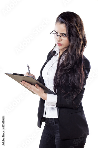 young serious business woman writing on her clipboard
