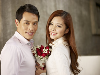 happy asian young lovers smiling with flowers