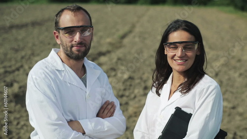 scientists smiling to the camera and standing in the field