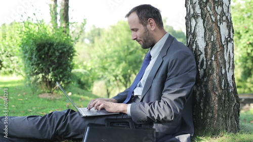 businessman working on laptop and sitting on the grass