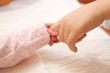 . Newborn baby holding finger of older child.