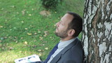 businessman relaxing under the tree